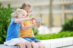 Duas irmãs mais nova bonitos que jogam o jogo móvel exterior em seus telefones espertos Foto de Stock