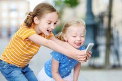 Duas irmãs mais nova bonitos que jogam o jogo móvel exterior em seus telefones espertos Imagens de Stock