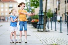 Duas irmãs mais nova bonitos que jogam o jogo móvel exterior em seus telefones espertos Imagem de Stock Royalty Free