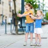 Duas irmãs mais nova bonitos que jogam o jogo móvel exterior em seus telefones espertos Foto de Stock Royalty Free