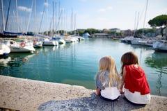 Duas irmãs mais nova bonitos que olham iate pequenos no porto em Desenzano del Garda no dia bonito do outono Imagens de Stock