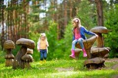 Duas irmãs mais nova bonitos que têm o divertimento em cogumelos de madeira gigantes fotos de stock royalty free