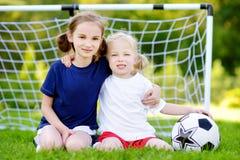 Duas irmãs mais nova bonitos que têm o divertimento que joga um jogo de futebol Foto de Stock