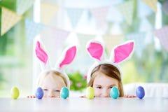 Duas irmãs mais nova bonitos que vestem as orelhas do coelho que jogam o ovo caçam na Páscoa Fotografia de Stock Royalty Free