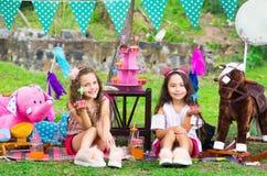Duas irmãs mais nova caucasianos bonitas que realizam em suas mãos um queque delicioso no ar livre, no parque no verão ensolarado Imagens de Stock