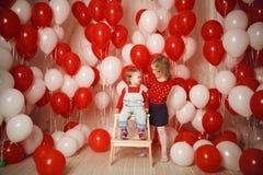 Duas irmãs mais nova com os balões vermelhos e brancos Imagem de Stock