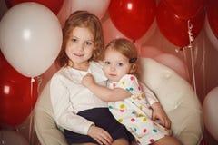 Duas irmãs mais nova com os balões vermelhos e brancos Foto de Stock Royalty Free