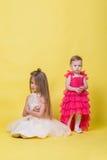 Duas irmãs nos vestidos em um fundo amarelo olham em sentidos diferentes e ofenderam Fotografia de Stock Royalty Free