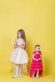 Duas irmãs nos vestidos em um fundo amarelo olham em sentidos diferentes e ofenderam Imagem de Stock Royalty Free