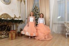 Duas irmãs novas no branco com vestidos do pêssego Fotos de Stock