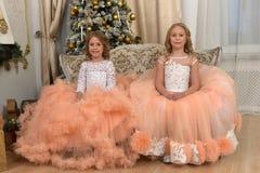 Duas irmãs novas no branco com vestidos do pêssego Imagem de Stock