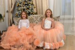 Duas irmãs novas no branco com vestidos do pêssego Imagem de Stock Royalty Free