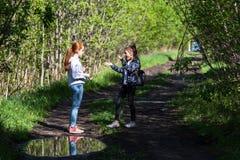 Duas irmãs ou amigas das meninas estão falando emocionalmente no parque Fotografia de Stock Royalty Free