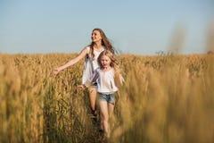 Duas irmãs que correm no trigo arquivado fotografia de stock royalty free