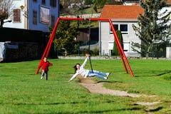Duas irmãs que jogam no campo de jogos, dia ensolarado Fotografia de Stock