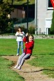 Duas irmãs que jogam no campo de jogos, dia ensolarado Fotos de Stock Royalty Free