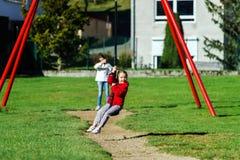 Duas irmãs que jogam no campo de jogos, dia ensolarado Imagens de Stock
