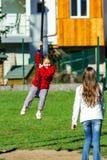 Duas irmãs que jogam no campo de jogos, dia ensolarado Imagens de Stock Royalty Free