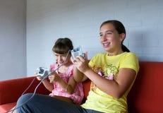 Duas irmãs que jogam os jogos video Fotos de Stock Royalty Free