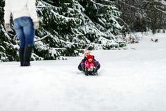 Duas irmãs que montam no dia de inverno dos trenós Fotos de Stock