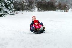 Duas irmãs que montam no dia de inverno dos trenós Foto de Stock
