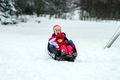 Duas irmãs que montam no dia de inverno dos trenós Imagem de Stock Royalty Free