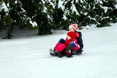 Duas irmãs que montam no dia de inverno dos trenós Imagens de Stock