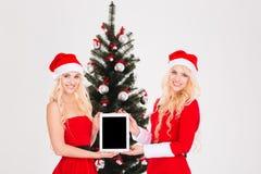 Duas irmãs que mostram o portátil com a tela vazia perto da árvore de Natal imagens de stock