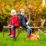 Duas irmãs que sentam-se em um banco no dia do outono Imagem de Stock Royalty Free