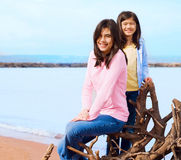 Duas irmãs que sentam-se pela costa do lago no verão Fotos de Stock Royalty Free
