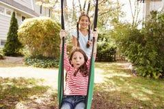 Duas irmãs que têm o divertimento no balanço do jardim em casa fotos de stock