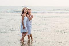 Duas irmãs que têm o divertimento no mar no por do sol imagens de stock royalty free