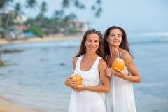 Duas irmãs que têm o divertimento no mar no por do sol fotografia de stock royalty free