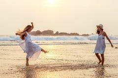 Duas irmãs que têm o divertimento no mar no por do sol foto de stock royalty free