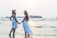 Duas irmãs que têm o divertimento no mar no por do sol fotografia de stock