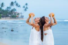 Duas irmãs que têm o divertimento no mar no por do sol fotos de stock