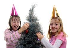 Duas irmãs que vestem a árvore de Natal fotos de stock royalty free