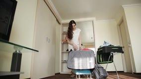 Duas irmãs recolhem coisas em uma mala de viagem em uma sala de hotel video estoque