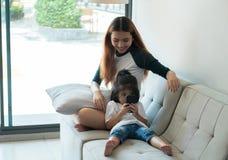 Duas irmãs usam o telefone celular e o assento no sofá na casa com r Imagem de Stock