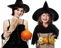 Duas irmãs felizes com hallowen máscaras da bruxa Imagens de Stock Royalty Free