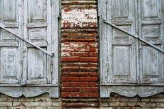 Duas janelas brancas de madeira velhas foram destruídas no tempo Parede de tijolo fotografia de stock