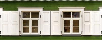 Duas janelas com as cortinas brancas abertas em uma casa de madeira velha Fotografia de Stock