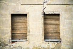 Duas janelas de madeira amarelas sujas marrons em uma fachada rachada quebrada amarela cinzenta de uma casa abandonada abandonada Fotos de Stock