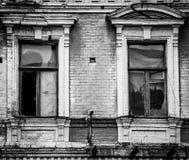 Duas janelas de madeira quebradas na fachada do tijolo Fotos de Stock Royalty Free