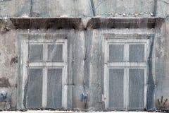 Duas janelas na fachada da malha fechado da casa velha para o repai fotos de stock