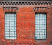 Duas janelas velhas com blocos de vidro quadrados em velho vestido abaixo da construção da fábrica Foto de Stock Royalty Free