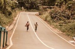 Duas jovens crianças que correm com os pés descalços em uma rua Foto de Stock Royalty Free