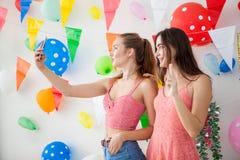 duas jovens mulheres alegres que comemoram tomam o selfie junto em novo fotos de stock royalty free