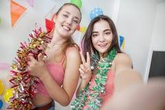 duas jovens mulheres alegres que comemoram tomam o selfie junto em novo fotos de stock