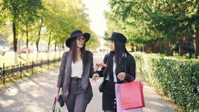 Duas jovens mulheres atrativas estão andando das lojas ao longo dos sacos de papel levando da rua bonita com compras e fala filme